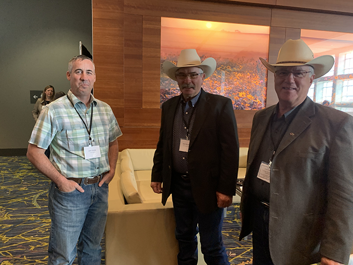 Simmental and SimAngus producers John Irvine (left), Kent Brunner, and Willie Altenberg catching up in the hall.